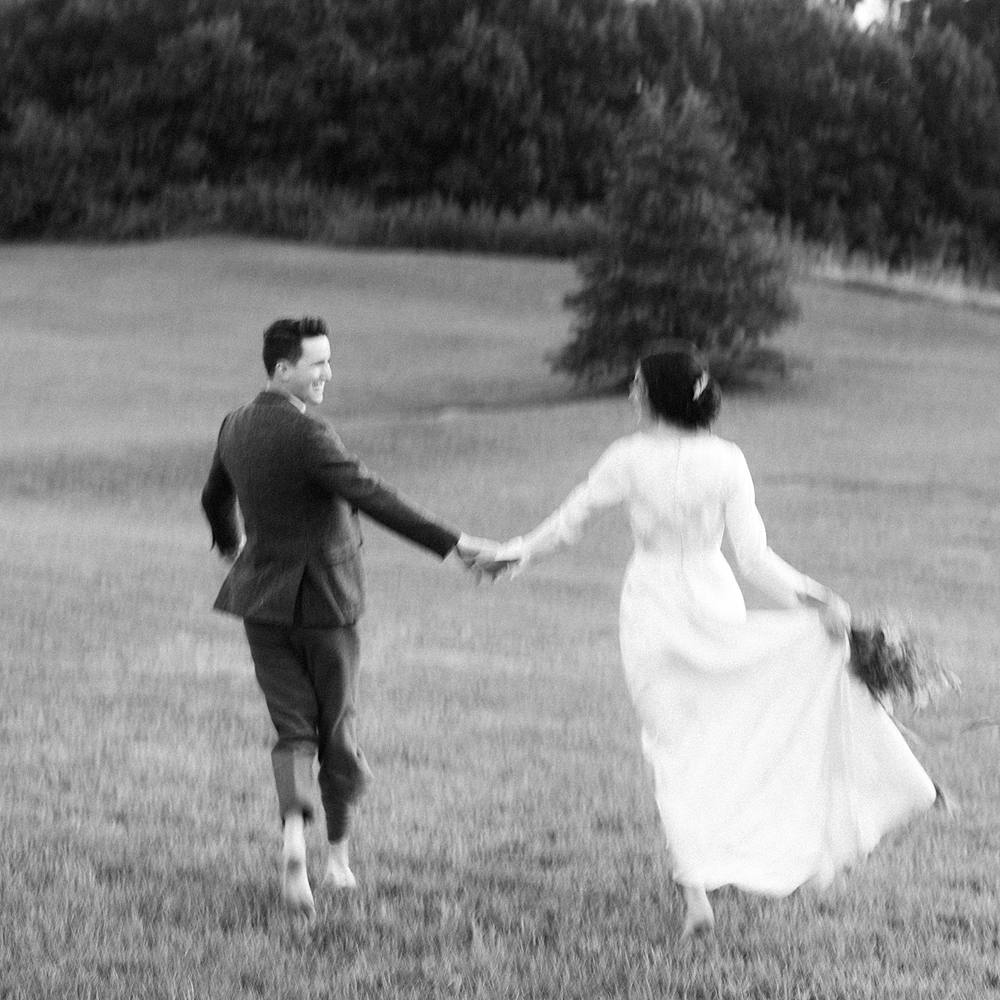 black and white film portrait of blurry wedding couple running at hotel domestique in south carolina with vintage dress