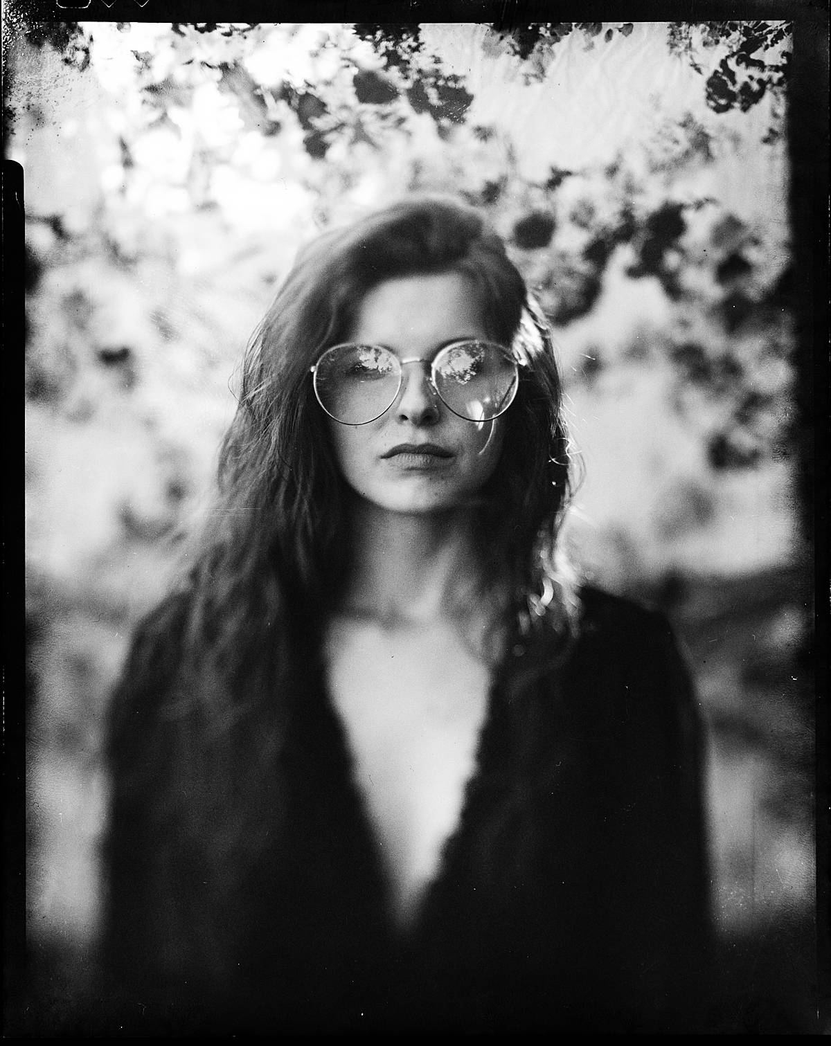 4x5 large format film portrait on black and white expired kodak t-max 400 film of a girl in black dress and sunglasses