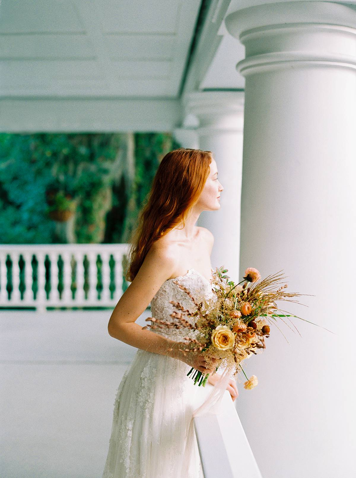 charleston bride on her wedding day on veranda overlooking magnolia plantation and gardens with bouquet