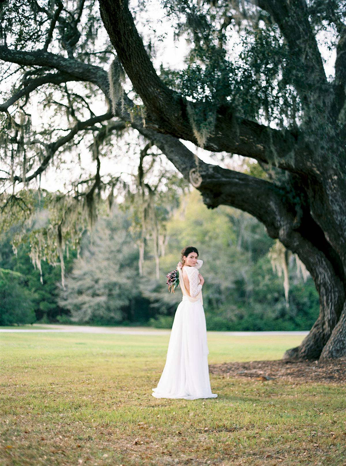 wingate plantation oak trees with charleston south carolina bride during wedding in bodysuit dress at sunset