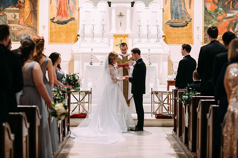 bride and groom at alter of st marys roman catholic church in downtown charleston for black tie february wedding