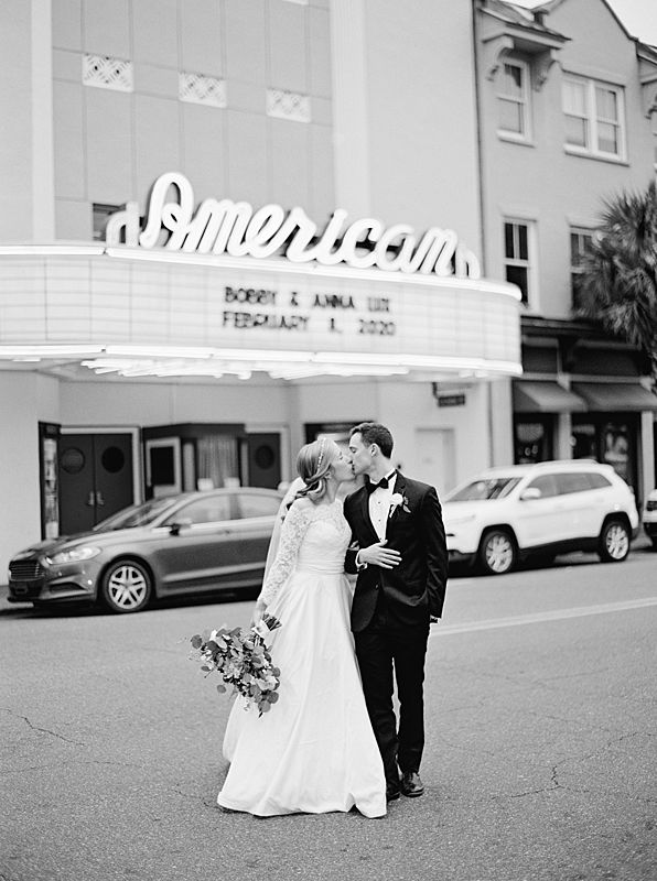bride and groom black and white film portrait in front of charleston's american theater for william aiken house wedding