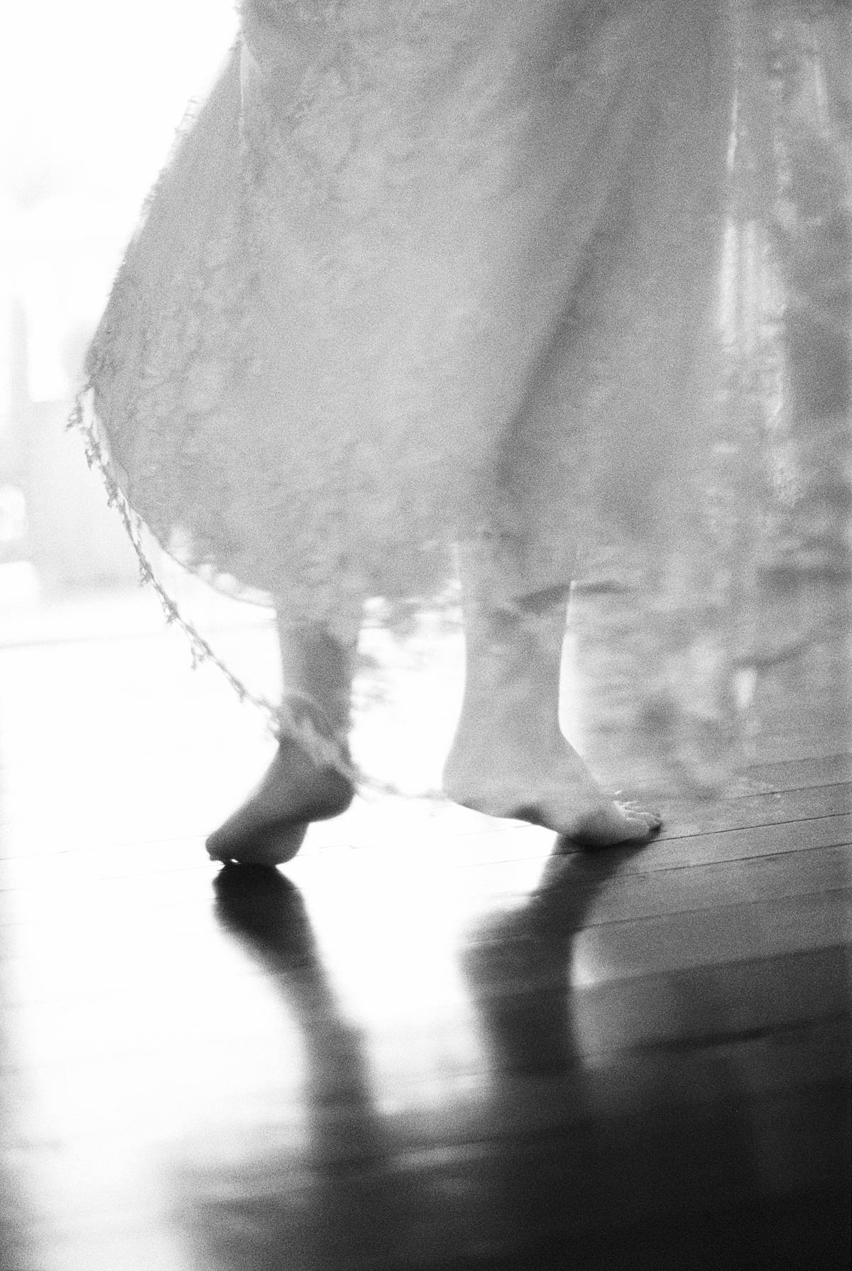 charleston bride in boudoir robe running up stairs at 86 cannon wedding venue dancing barefoot on black and white film