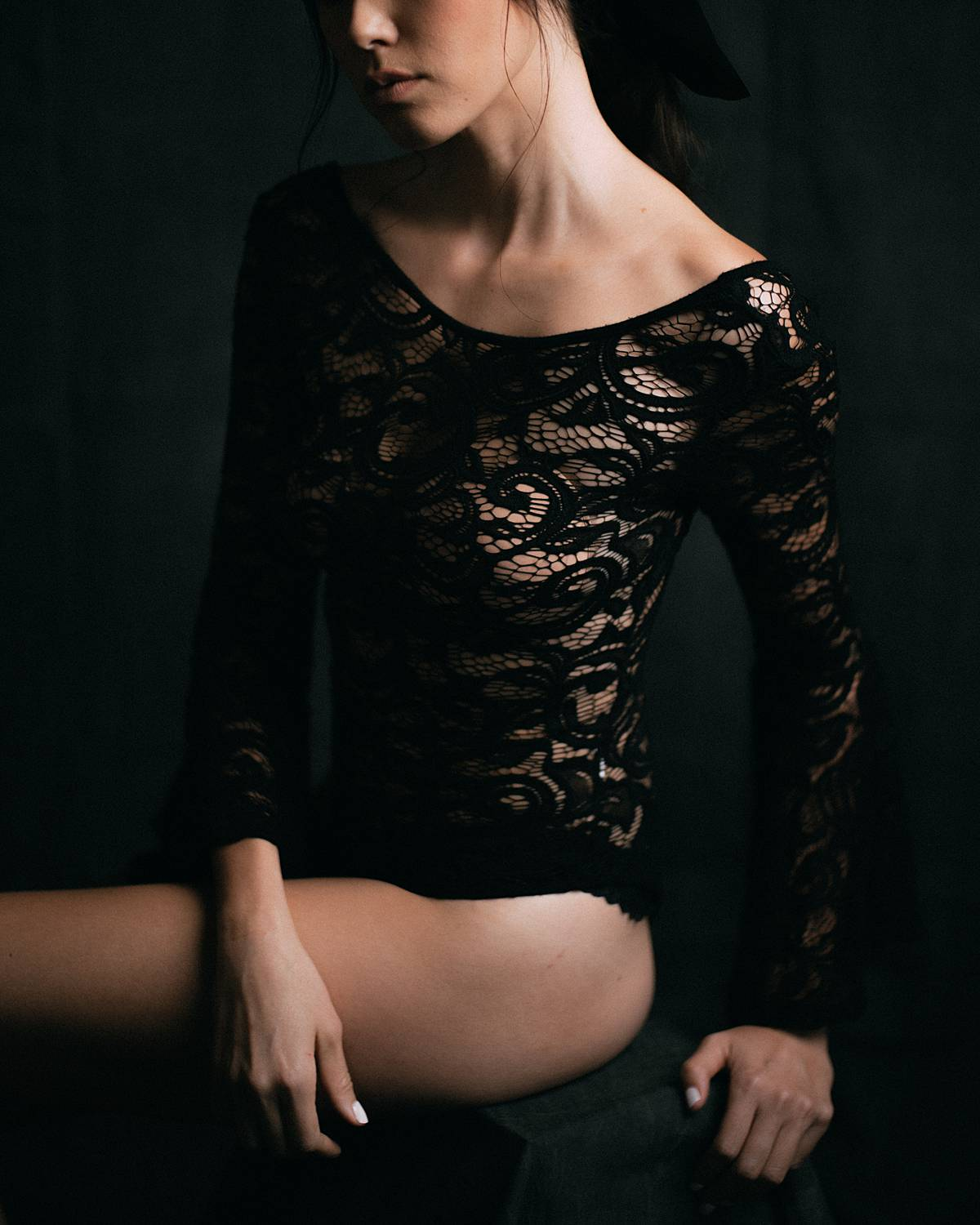 charleston studio boudoir with rembrandt lighting and grey muslin backdrop with bride in black lace longsleeve bodysuit