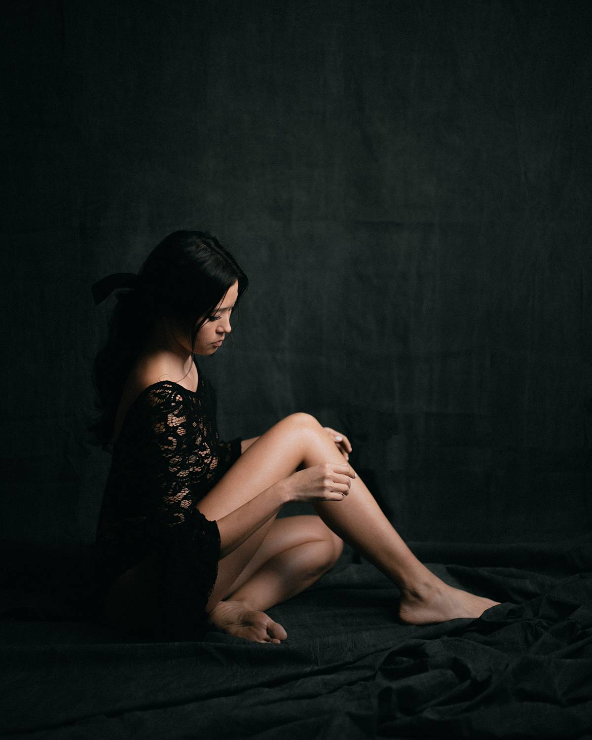 charleston studio boudoir portrait dark backdrop with soft window light and girl in black lace bodysuit