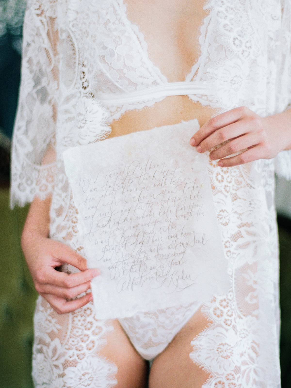 charleston bridal boudoir on film with bride holding hand made letter at wingate plantation in lingerie and lace robe