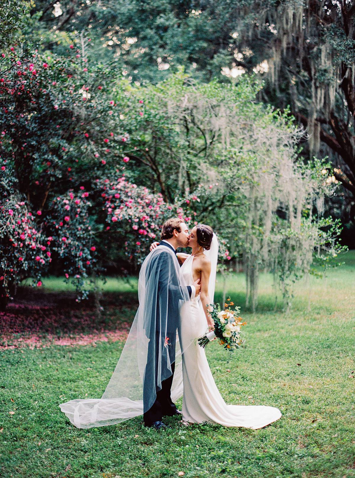 wedding portrait at legare waring house in charleston sc on kodak portra 800 film with blooming flowers on oak trees