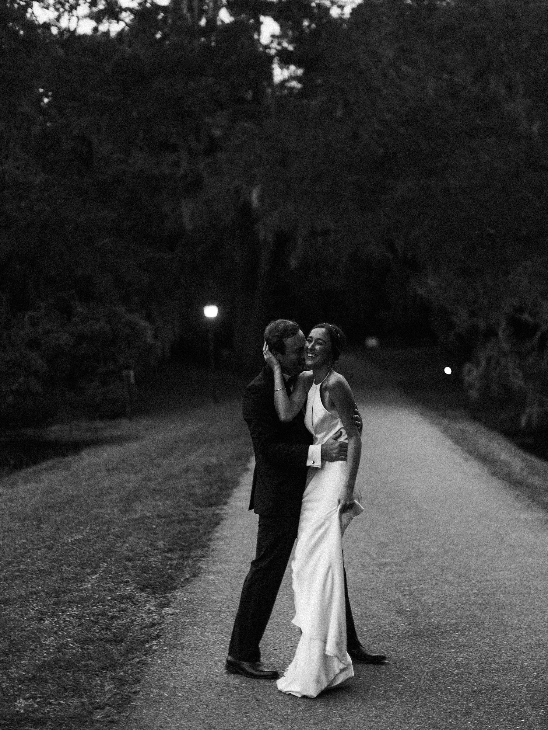 charleston sc wedding couple in black and white at legare waring house wedding with bride laughing while dancing
