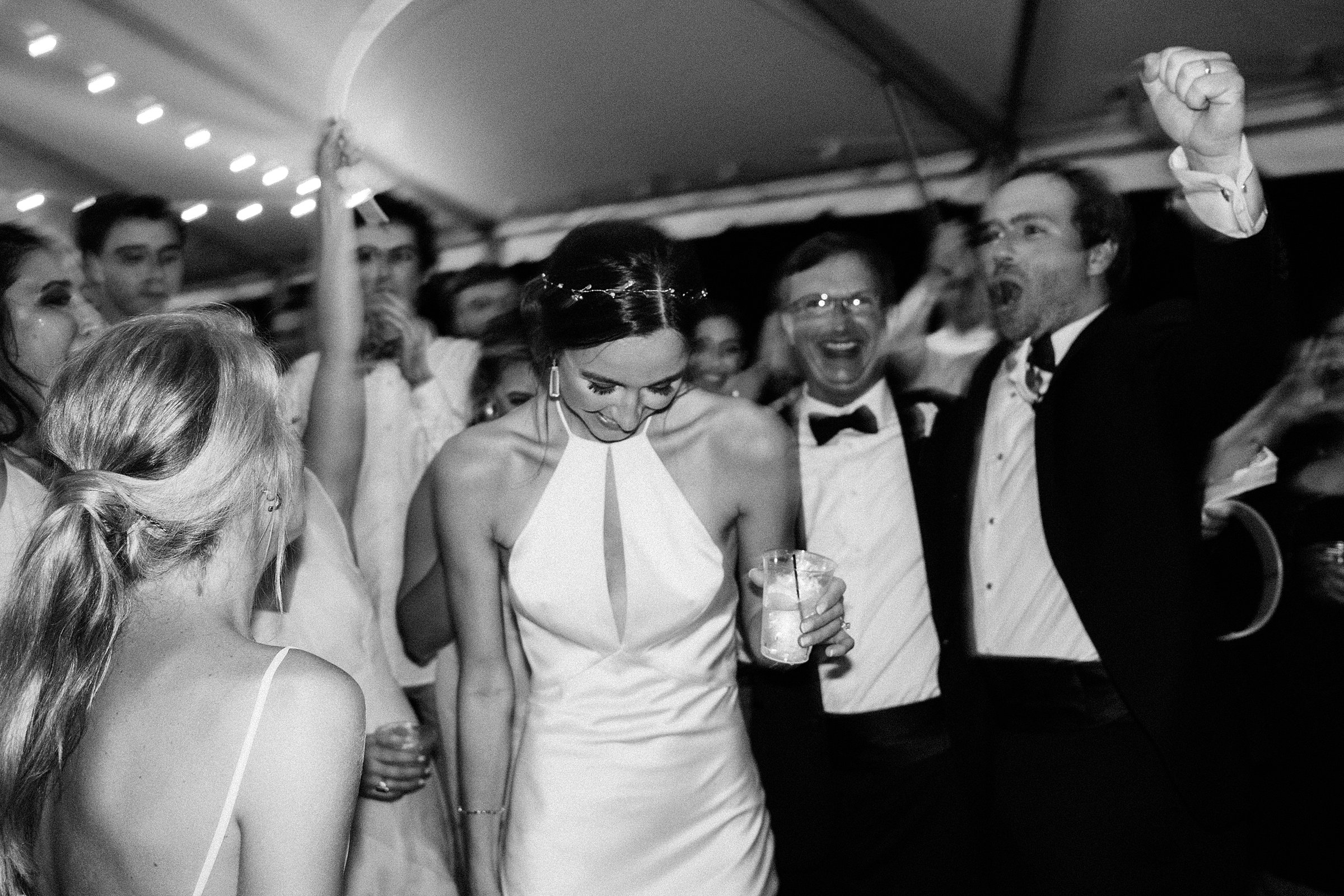 bride laughing during wedding reception in black and white photograph at legare waring charleston sc venue