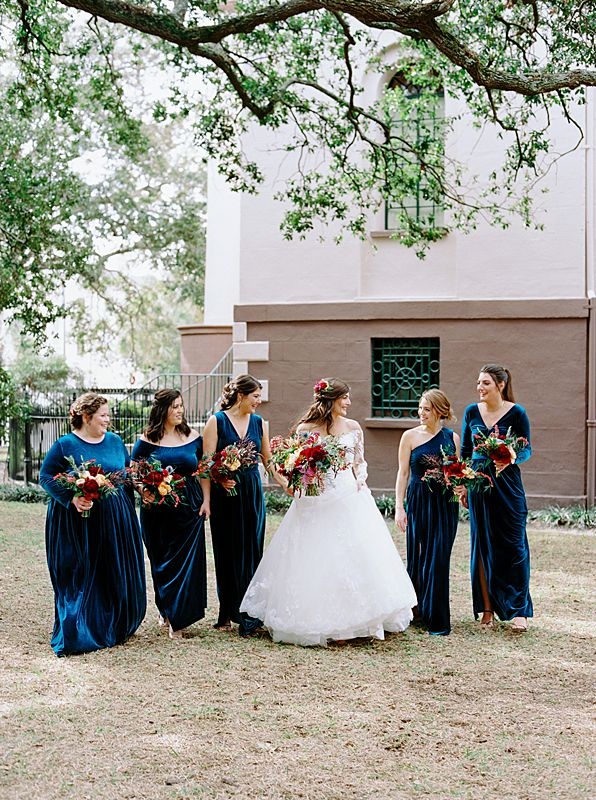 blue velvet bridesmaids dresses in charleston sc for fall wedding with bride holding jewel tone bouquet on kodak film