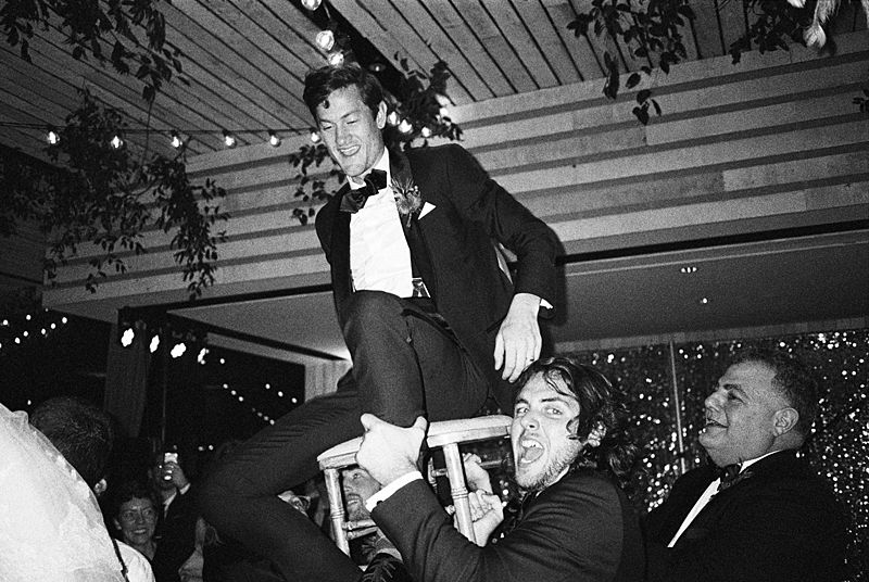 groom in chair during horah dance at a charleston sc wedding captured on kodak p3200 film with a contax t3
