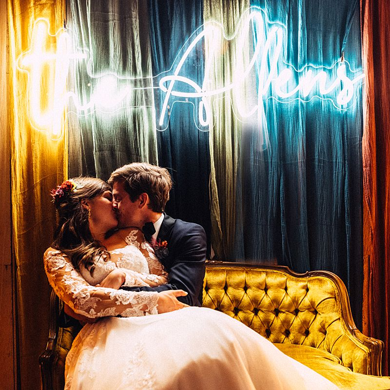 bride and groom kissing in front of custom made sign with their newlywed name in neon at this charleston sc wedding