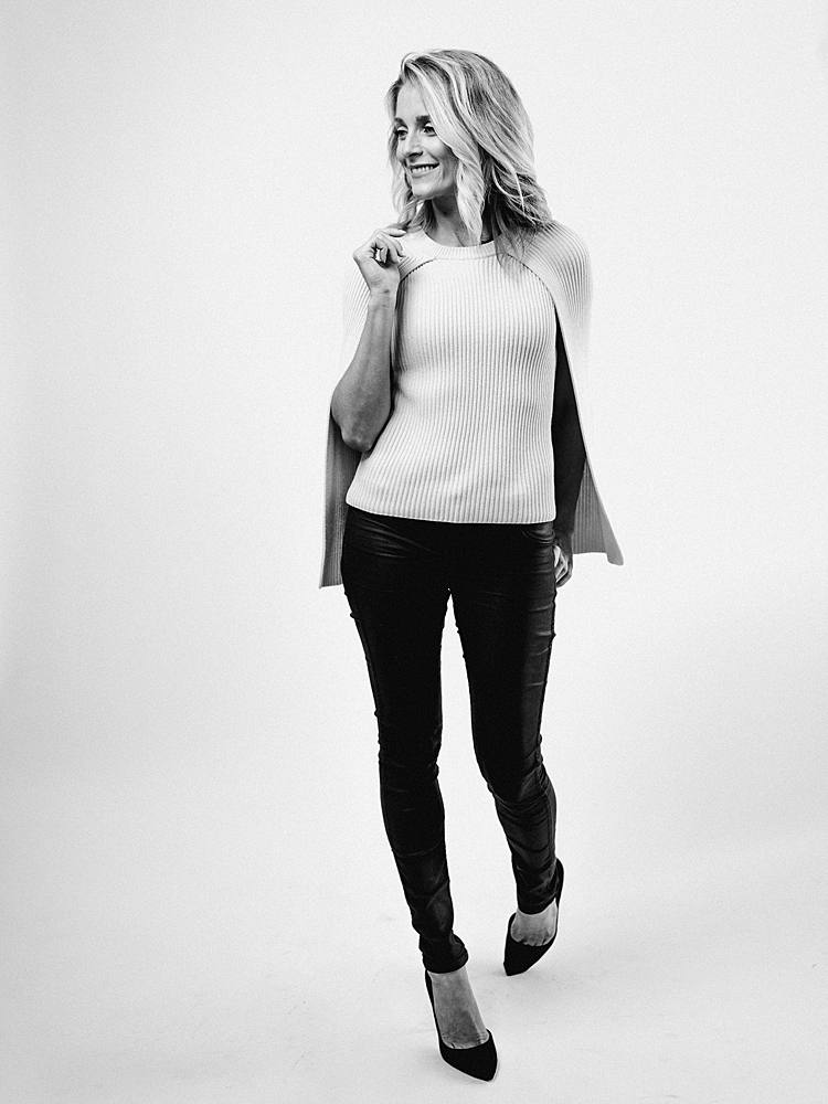 branding portrait in studio with charleston sc wedding planner with black and white re-brand style with black pants and cream sweater
