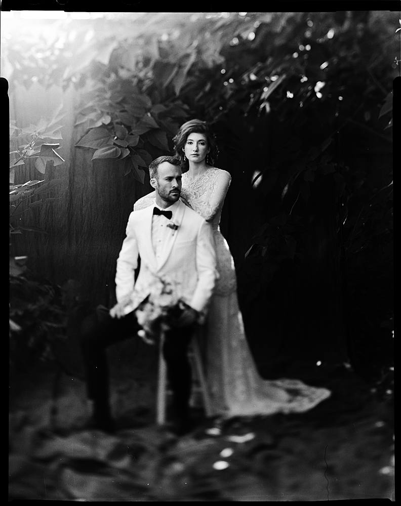 large format black and white film portrait of bride and groom in charleston sc outdoor studio backdrop