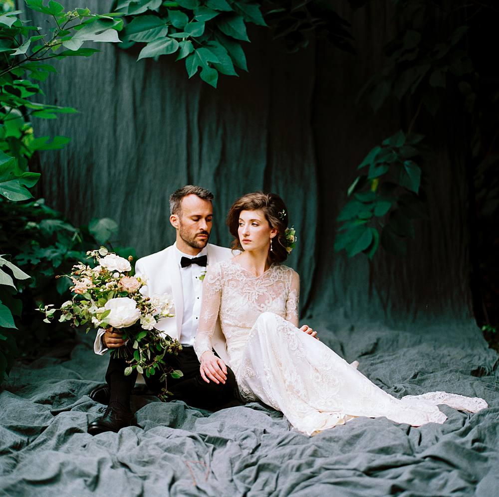 hasselblad and kodak film portrait of a charleston bride and groom in lace cream dress and white dinner jacket tuxedo in outdoor wedding portrait studio