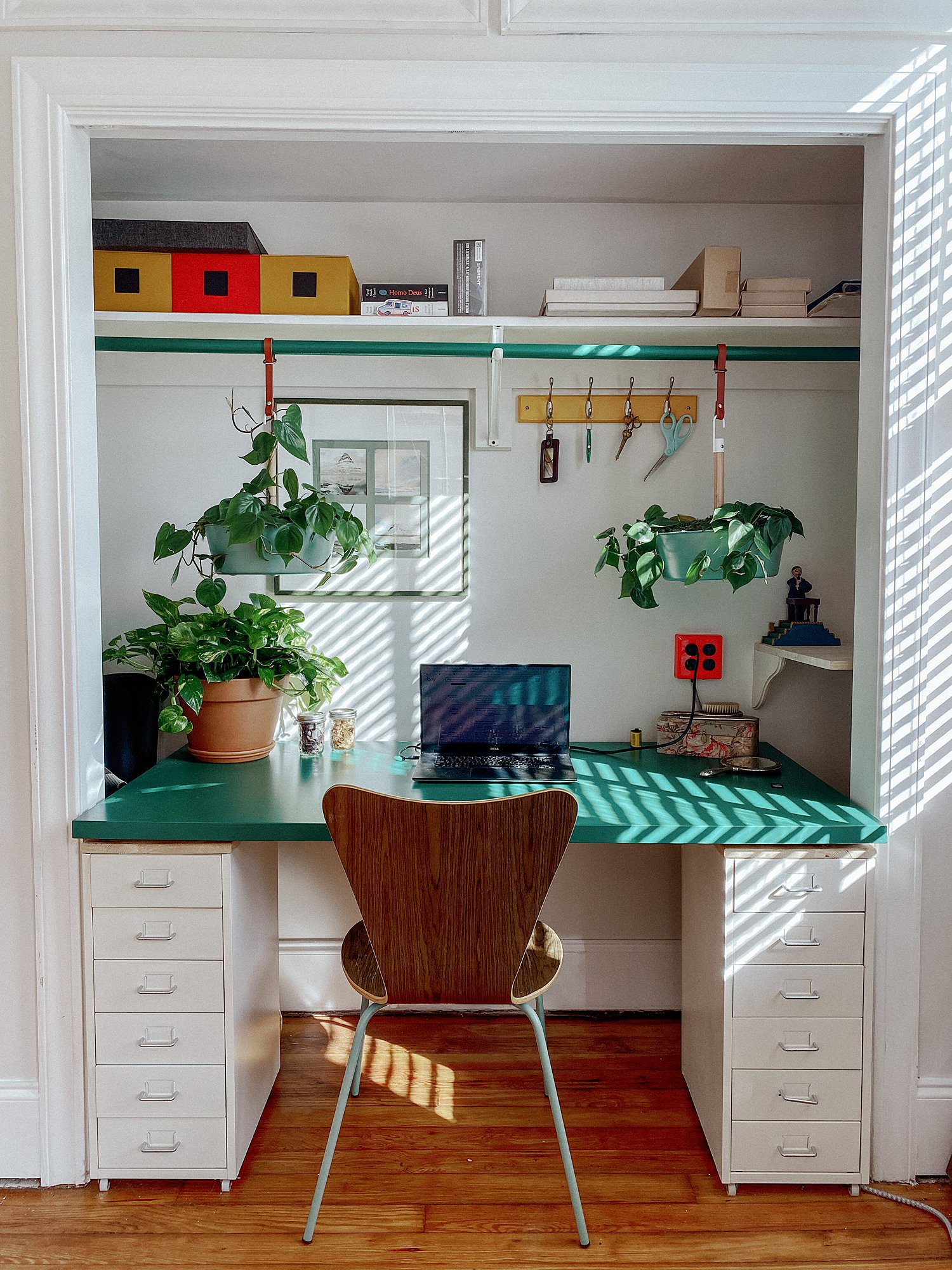 hanging plants in a primary color mid century styled eclectic desk space built into my home photography studio closet